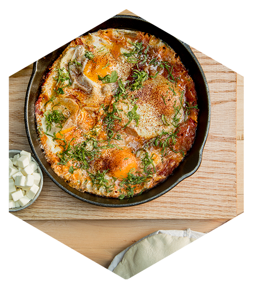Shakshuka. Huevos pochados en salsa especiada de jitomate y pimiento, cilantro, comino y cebolla.