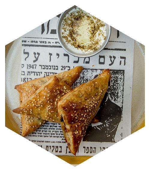 Bourekas. Empanadas de hojaldre rellenas de espinaca y queso feta con labneh hecho en casa, za ́atar y aceite de oliva.