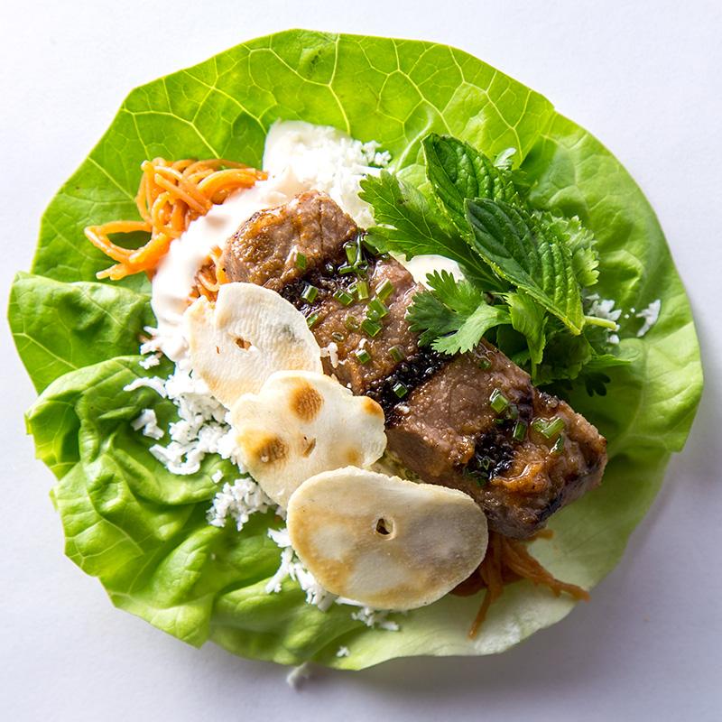 Ssäm de fideo seco, lechuga francesa, filete de res con marinado vietnamita, cacahuate, yerbabuena, crema agria, cebolleta, chips de ajo macho.