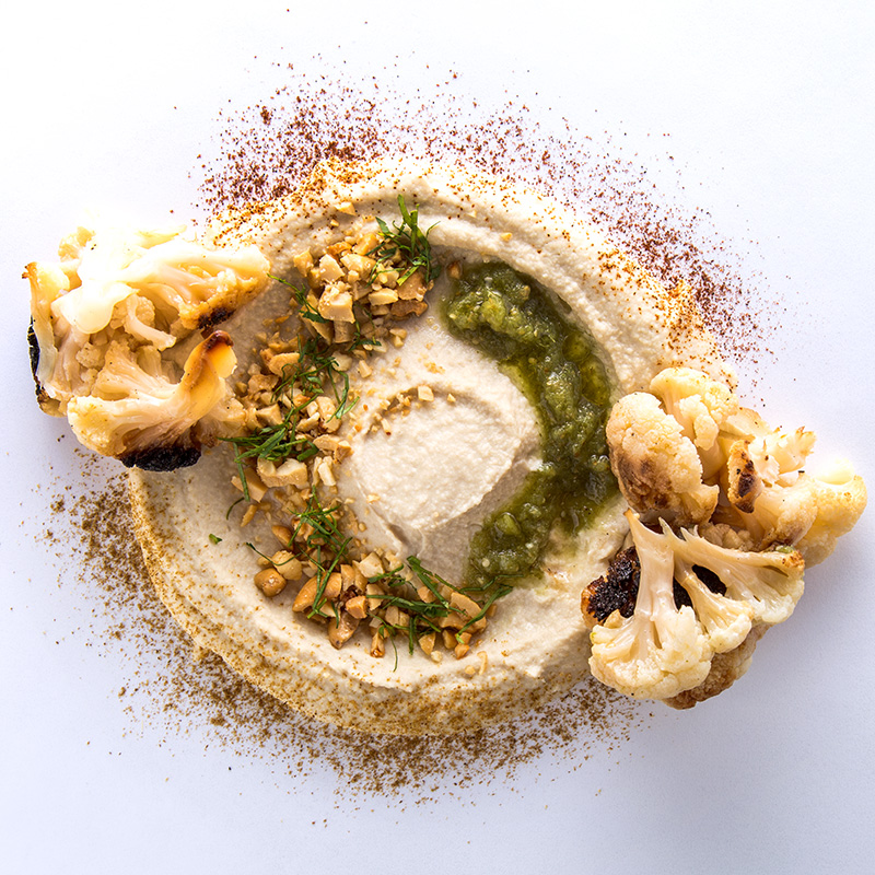 Hummus, comino, chiles ahumados, cilantro, coliflor rostizada, nuez de la India, aceite de oliva y zhoug.