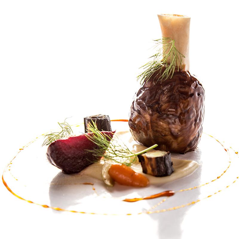 Chamorro de cerdo glaseado con miel y cardamomo, zanahoria y betabel a la sal, eneldo, cebollas cambray y puré de papa.